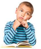 Young boy is daydreaming while reading book — Stock Photo