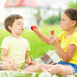 Little girl and boy are blowing soap bubbles — Stock Photo #50358233