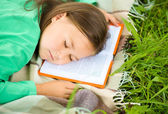 Girl is sleeping on her book outdoors — Stock Photo