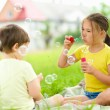 Little girl and boy are blowing soap bubbles — Stock Photo #50571375