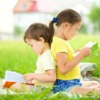 Little girl and boy are reading book outdoors — Stock Photo