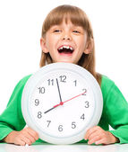Petite fille tient la grosse horloge — Photo