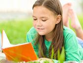 Holčička je čtení knihy venku — Stock fotografie