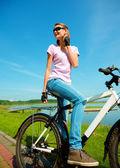 Mladá žena sedí na kole — Stock fotografie