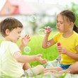 Little girl and boy are blowing soap bubbles — Stock Photo #50637185