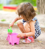 Little girl is playing with sand in playground — Stockfoto