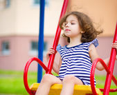 Young happy girl is swinging in playground — Stock Photo