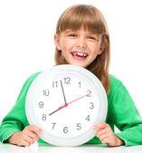Little girl is holding big clock — Stock Photo
