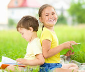 Little girl and boy are reading books outdoors — Stock Photo
