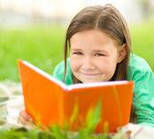 Liten flicka läser en bok utomhus — Stockfoto