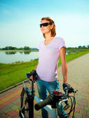 Young woman is standing behind bicycle — Photo