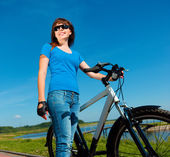 Young woman is standing in front of her bicycle — Photo
