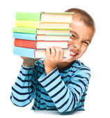 Little boy is holding a pile of books — Stock Photo