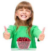 Cute girl is eating cherries showing thumb up sigh — Stockfoto