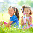 Two little girls are blowing soap bubbles — Stock Photo #51119273