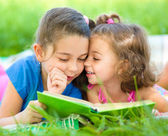 Two little girls are reading book — Foto de Stock