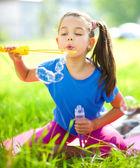 Little girl is blowing a soap bubbles — 图库照片