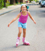 Happy little girl is skating on rollers — Stock Photo