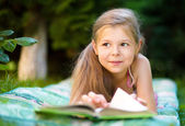 Little girl is reading a book outdoors — Stock Photo