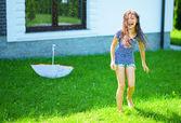 Happy girl is playing under rain — Stock Photo