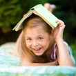 Little girl is hiding under book outdoors — Stock Photo #51473301
