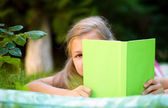 Little girl is hiding behind book outdoors — Stock Photo