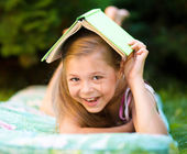 Little girl is hiding under book outdoors — Stock Photo