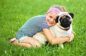Little girl and her pug dog on green grass — Stock Photo