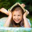 Little girl is hiding under book outdoors — Stock Photo #51511681