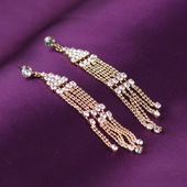 Earrings on purple background — Stock Photo