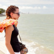 Young girl in sunglasses looking at the sea  — Stok fotoğraf