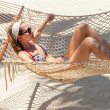 Stock Photo: Young beautiful girl taking sunbath swinging in hammock