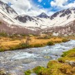 View to snow on Caucasus mountains over clear water stream near — Stock Photo