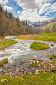 View to snow on Caucasus mountains over motion blurred stream ne — Foto Stock