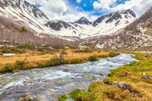 View to snow on Caucasus mountains over clear water stream near — Stok fotoğraf