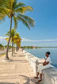 Paseo el Prado embankment with local woman sitting — Stock Photo