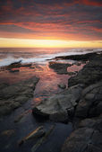 Sunset over rocky coastline — Stock Photo