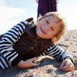 Stock Photo: Smiling boy lying on beach.