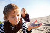 Dítě s pískem v ruce na pláži. — Stock fotografie