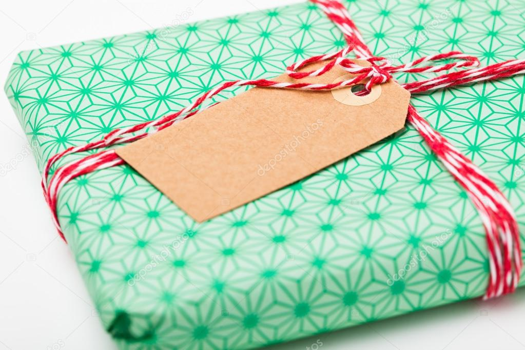 Close-up of simple gift package with green wrapping and plain cardboard tag — Stock Photo #14368851