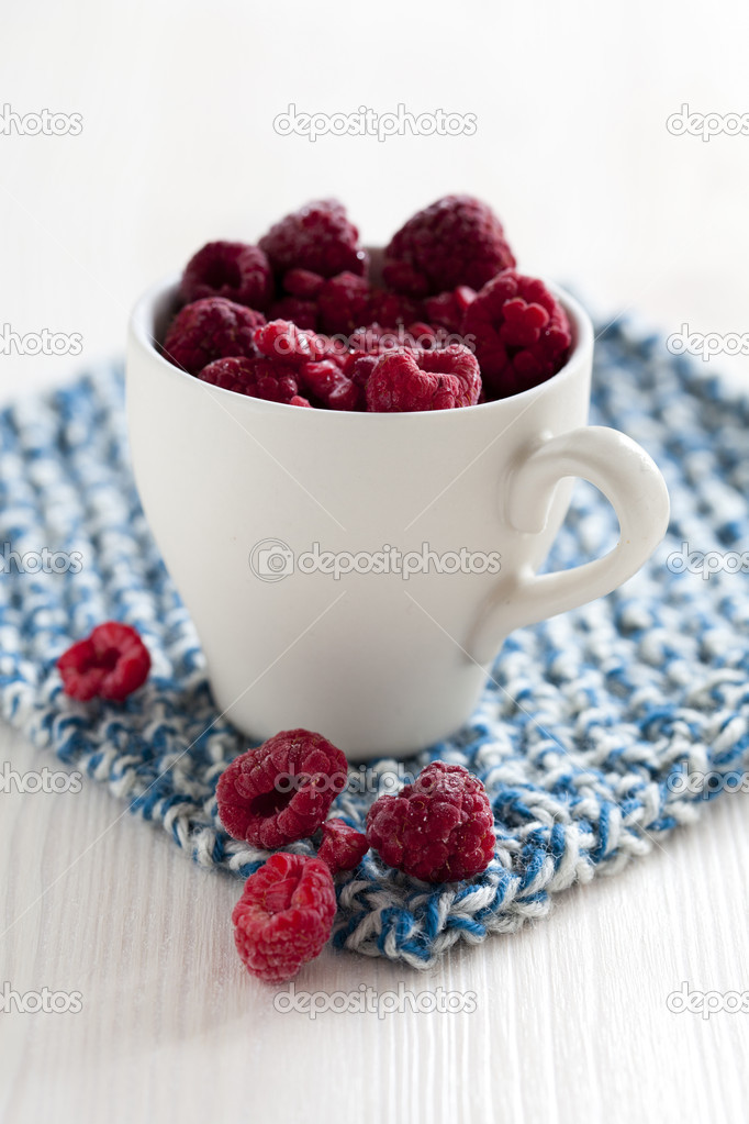 Closeup of fresh raspberries in white cup on a blue mat — Stock Photo #14749935