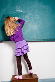 Young girl drawing on chalkboard — Stockfoto