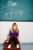 Smiling young girl in front of chalkboard — Foto Stock