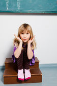 Young girl blowing kiss in classroom — Foto Stock