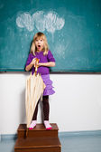 Surprised young girl with umbrella indoors — Stock Photo