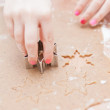 Cutting gingerbread shapes from dough — Stock Photo #21616137