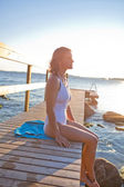 Attractive woman sitting on pier — Stock Photo