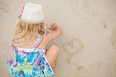 Young girl drawing heart shapes in sand — Stock Photo