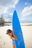 Happy young girl with surfboard at beach — Stock Photo