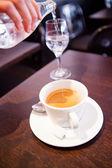 Kopje espresso en stromende water — Stockfoto